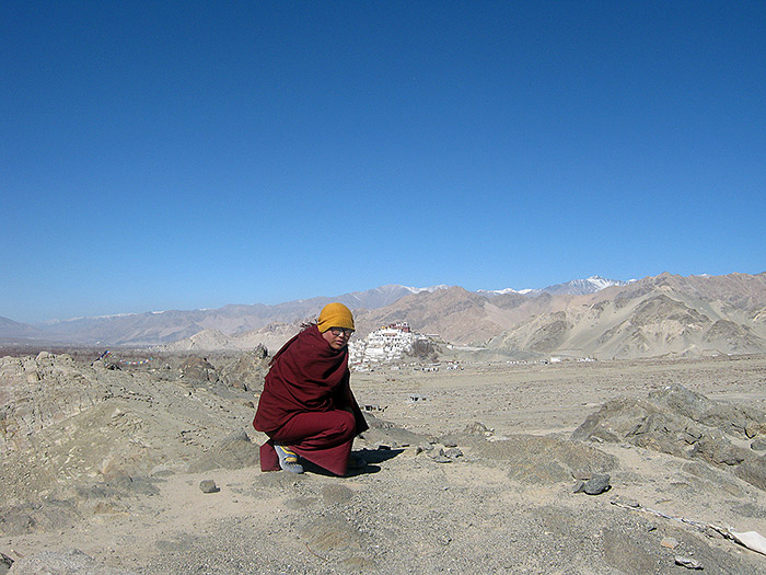 nun with thikse monastery in background